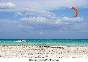 kitesurfing in Italy - A kitesurfer gliding at high speed...