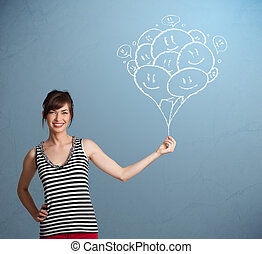 Happy woman holding smiling balloons drawing - Happy young...