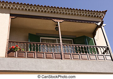 balcony with green shuttered windows and red flower