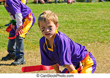 Youth flag football player with hands on knees.