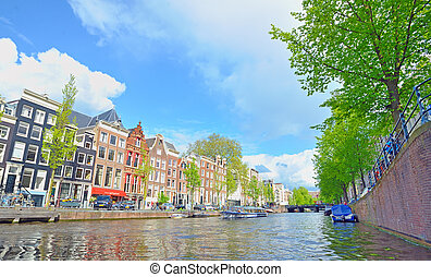 Traditional Houses and house boat along canal in Amsterdam,...