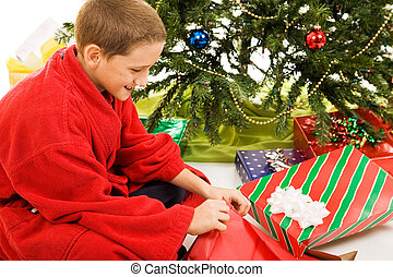 Boy Opens Christmas Present - Cute little boy opening his...