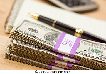 Stack of Money, Calculator, Paper and Pen