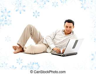 relaxed man with laptop computer and snowflakes