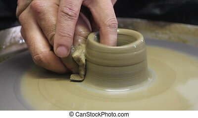 The hands of a potter, creating an earthen jar on the...