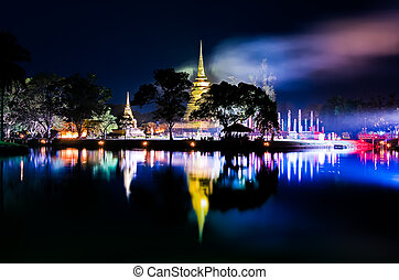 Buddhist colorful temple at night with lake reflection -...