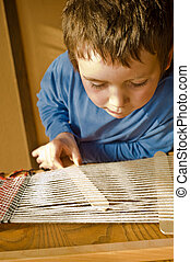 boy using loom - boy in blue preparing loom for weaving