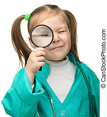 Cute little girl is playing doctor with magnifier, isolated...