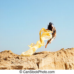 Beautiful young woman jumping in a desert