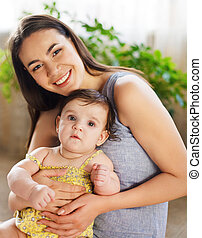 Mother with eight month old baby girl indoor - Happy smiling...