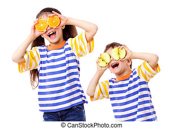 Two funny kids with fruits on eyes