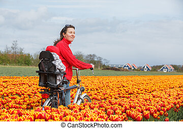 Family on bikes in spring flower fields - Cute young mother...