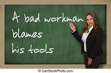 Teacher showing A bad workman blames his tools on blackboard...