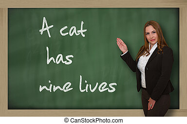 Teacher showing A cat has nine lives on blackboard -...