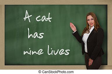 Teacher showing A cat has nine lives on blackboard -...