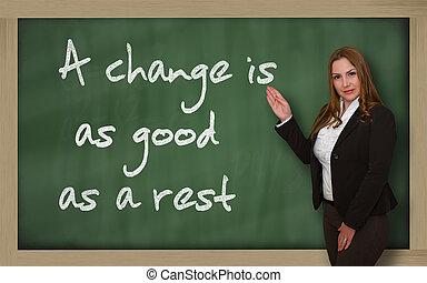 Teacher showing A change is as good as a rest on blackboard...