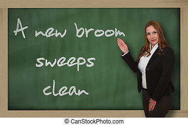 Teacher showing A new broom sweeps clean on blackboard -...