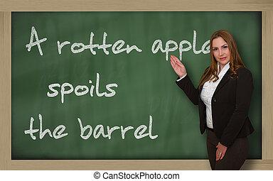 Teacher showing A rotten apple spoils the barrel on...