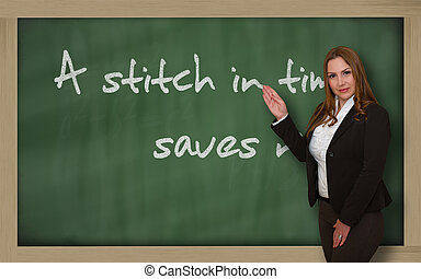 Teacher showing A stitch in time saves nine on blackboard -...