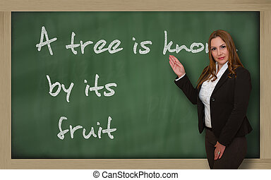 Teacher showing A tree is known by its fruit on blackboard -...