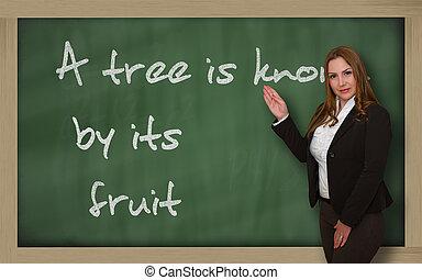 Teacher showing A tree is known by its fruit on blackboard -...