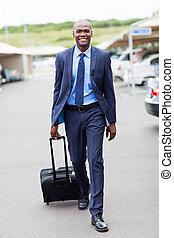 african businessman walking in airport - handsome african...
