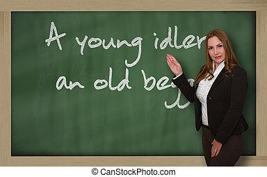 Teacher showing A young idler, an old beggar on blackboard -...