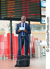 african businessman in airport standing in front of flight...
