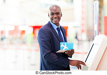 self service check in - african businessman using self...