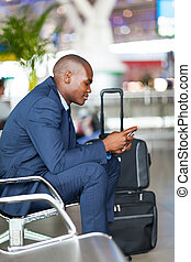 african businessman at airport - african businessman using...