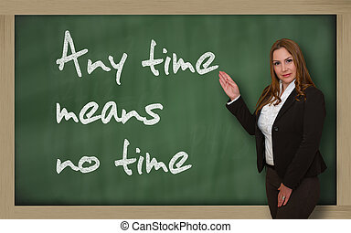 Teacher showing Any time means no time on blackboard -...