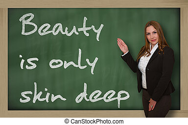 Teacher showing Beauty is only skin deep on blackboard -...