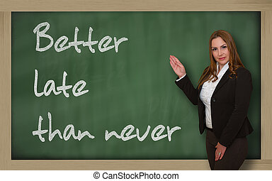 Teacher showing Better late than never on blackboard -...