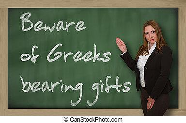 Teacher showing Beware of Greeks bearing gifts on blackboard...
