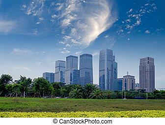 City and grass - City park under blue sky with Downtown...
