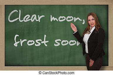 Teacher showing Clear moon, frost soon on blackboard -...