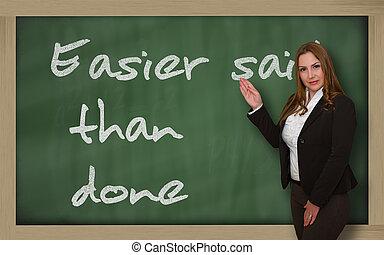 Teacher showing Easier said than done on blackboard -...