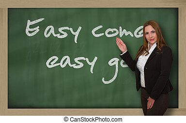 Teacher showing Easy come, easy go on blackboard -...