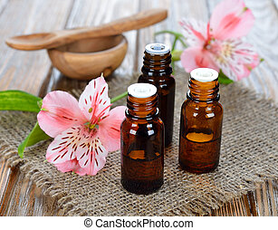 Essential oil - Essential oil and flowers on a brown...