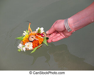 flowers on the river - arangement of flowers and candle on...
