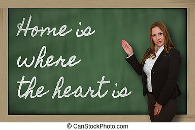 Teacher showing Home is where the heart is on blackboard