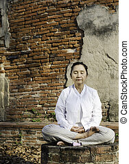 woman meditating in temple - Buddhist woman meditating...