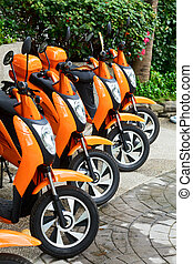 Scooters for rent - Orange scooter mototbikes parked in a...