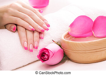 hands with rose petals and towel. Spa - female hands with...