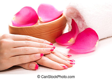 pink manicure with fragrant rose petals and towel. Spa
