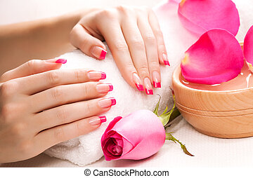 female hands with rose petals and towel. Spa - female hands...
