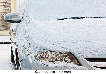 Car covered in fresh snow - front bonnet and lights of...