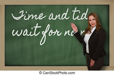 Teacher showing Time and tide wait for no man on blackboard...