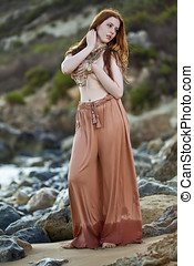 Beautiful woman with pale skin and long red hair wearing...