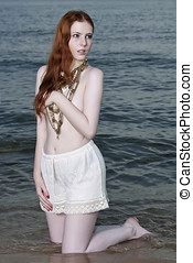 A beautiful woman with pale skin and red hair kneeling on a...